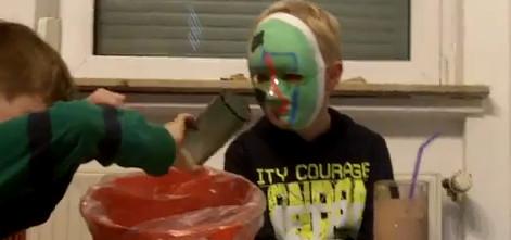 Junger Mensch mit grüner Maske betrachtet Gefäße
